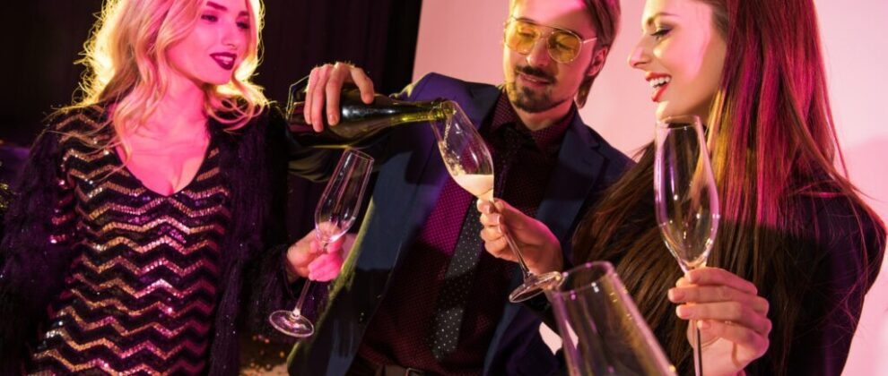 man pouring champagne into glasses on party, on pink