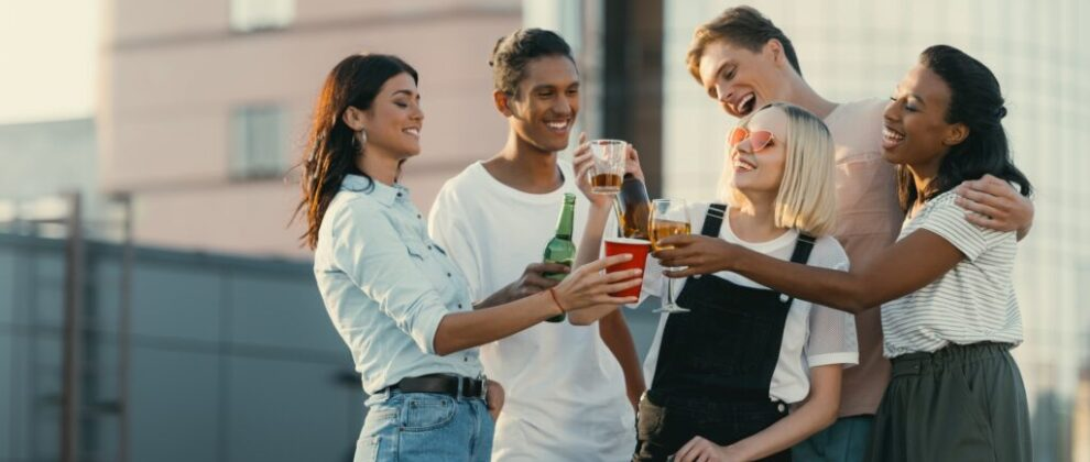 group of happy friends drinking alcohol on roof